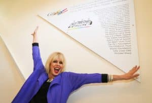 JOanna Lumley throws her arms wide as she unveils a plaque at the Grange, Bookham