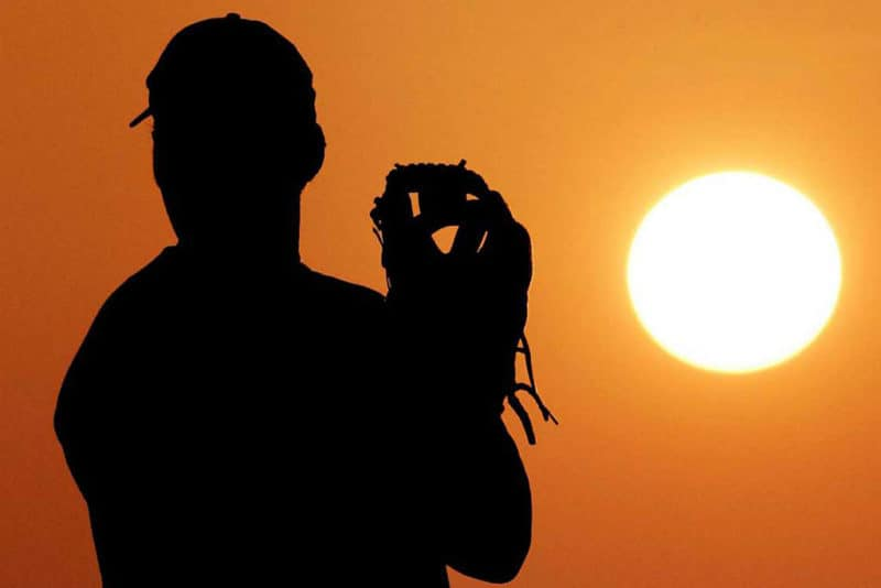 Silhouette of baseball pitcher with sun and orange sky behind him and